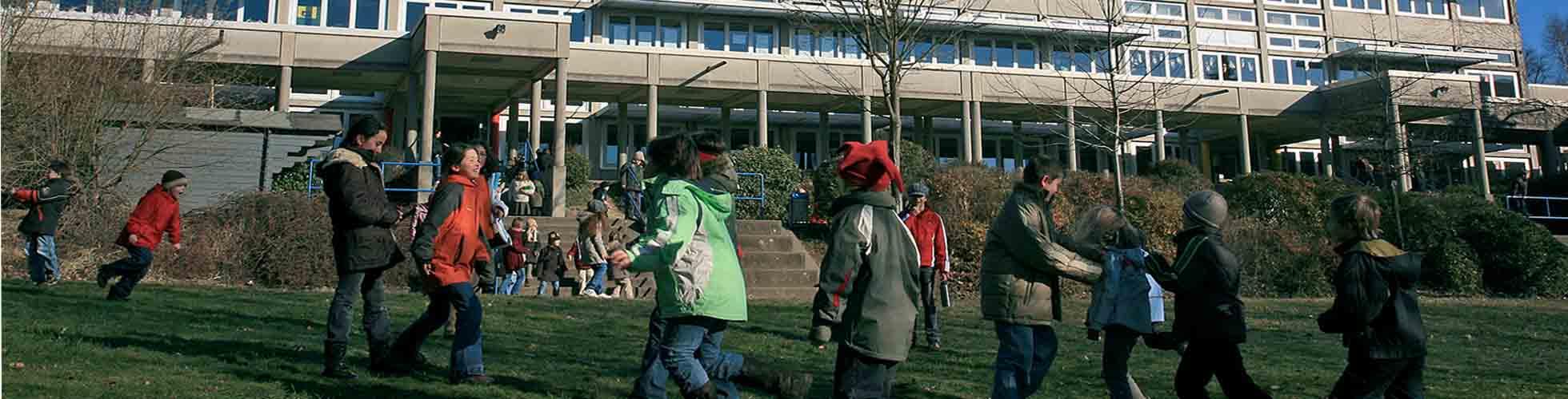 Spielende Kinder vor eine Schule