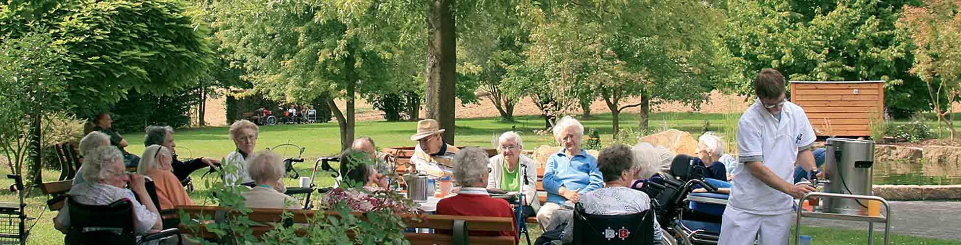 Seniorengruppe beim Kaffeetrinken im Garten