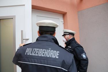 Gemeindevollzugsbedienstete vor einer Haustür.