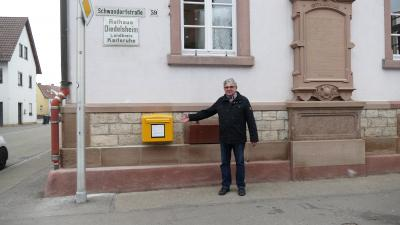 Stolz präsentiert Ortsvorsteher Martin Kern den neuen Briefkasten an der Ortsverwaltung Diedelsheim. Foto: Nina Kraus, Stadt Bre